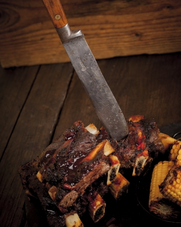 Beef ribs cooked on the barbeque and served with sweetcorn and a red wine souse