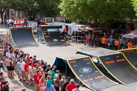 Athens, GA, USA - April 25, 2015:  A large crowd watches a young BMX pro perform spectacular tricks in the pro BMX competition at the annual Athens Twilight Criterium, on April 25, 2015 in Athens, GA.