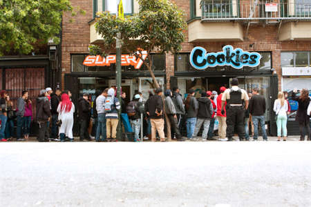 San Francisco, CA, USA - May 15, 2015:  A very long line of people waits to get into a new Cookies store in the Haight Ashbury section of San Francisco.  Cookies sells clothes and marijuana-related swag and accessories.