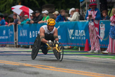 Photo pour Atlanta, GA, USA - July 4, 2015:  An athlete competing in the wheelchair portion of the Peachtree Road Race speeds toward the finish line in the annual Atlanta Independence Day event. - image libre de droit