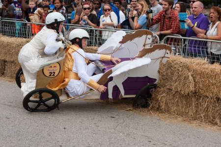Atlanta, GA, USA - October 24, 2015:  Competitors racing a soap box derby car designed like a Roman chariot crash into hay bales at the Red Bull Soap Box Derby on North Avenue in Atlanta, GA.