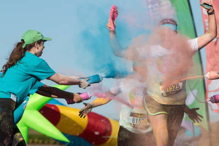 Hampton, GA, USA - April 2, 2016:  Volunteers douse runners with colored corn starch at The Color Run on April 2, 2016 in Hampton, GA.