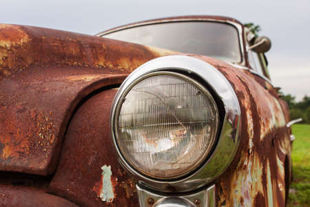 Photo for Cracked headlight on old rusted junkyard car - Royalty Free Image