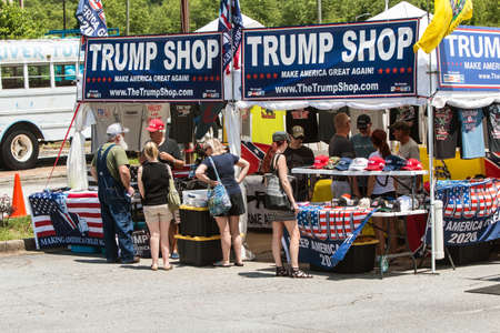 Helen, GA, USA - June 2, 2018:  People look over the merchandise at the Trump Shop, a popup outdoor store selling Donald Trump apparel and other items in a parking lot on June 2, 2018 in Helen, GA.