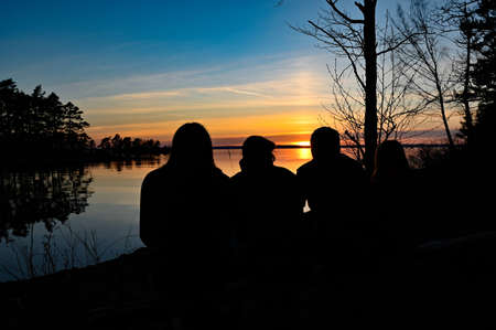 family of four looking at the sunset over a lake