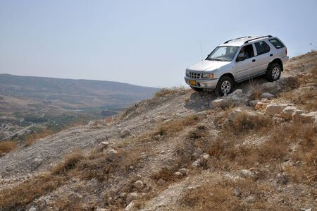 4x4 vehicle driving down hill in a stone desert