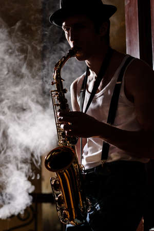 Jazz is his life. Handsome young jazzmen playing sax with a smoke on the background