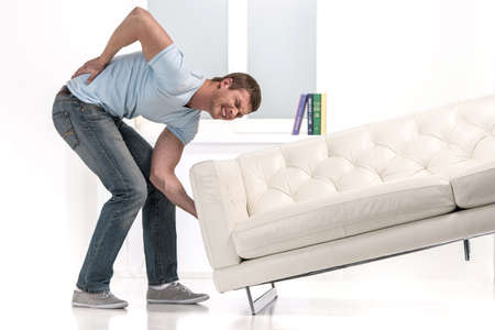 Handsome man lifting sofa and feeling pain. man droped sofa because of painful back
