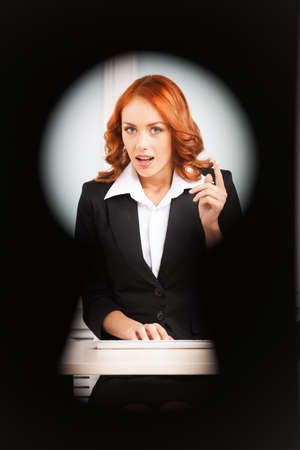 keyhole view of young pretty business woman. red-hair girl working on computer noticed