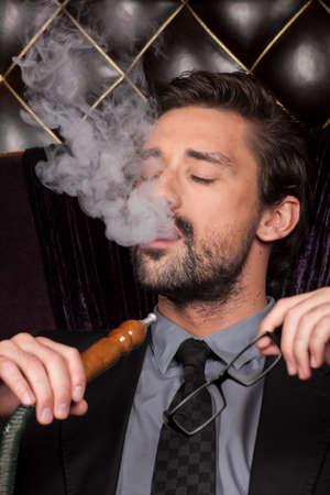 man smoking shisha at arabic restaurant. young man exhaling smoke with closed eyes