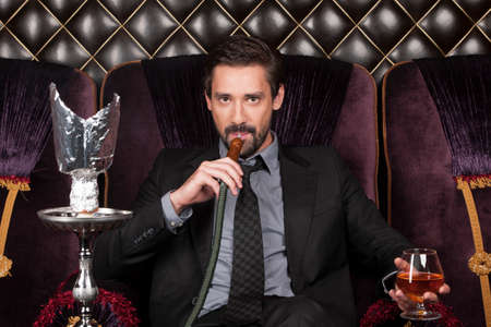 man sitting and inhaling shisha in restaurant. handsome businessman looking into camera and drinking