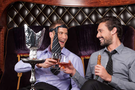 two young men smoke from shisha pipe. business friends drinking and fooling around