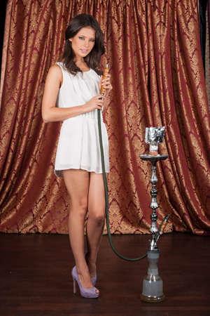 tall young woman holding hookah. sexy girl smoking turkish shisha and standing