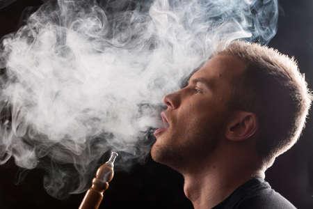 Close-up of man smoking traditional hookah pipe. man exhaling smoke on black background