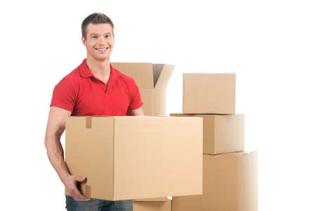 man holding moving box and smiling at camera. young man carrying carton boxes