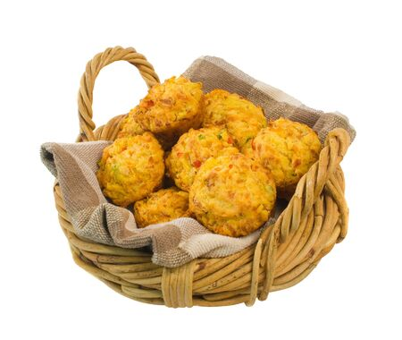 Delicious freshly baked savoury muffins in wicker basket isolated over white background