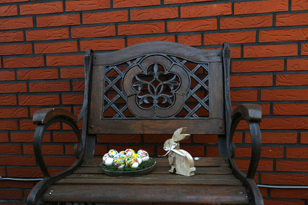 Photo pour Full view on easter eggs with wooden bunny on a chair in front of a brick wall with copy space and photographed on a sunny spring day - image libre de droit