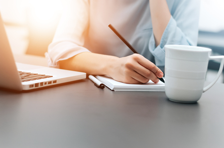 Photo pour Hand of businesswoman writing on paper in the office. - image libre de droit
