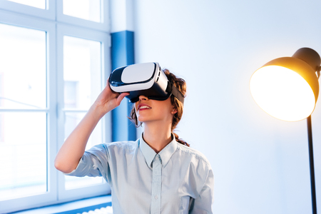 Woman wearing virtual reality goggles standing in a kitchen  VR