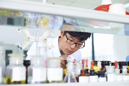 One male Chinese Laboratory scientist working at lab with test tubes