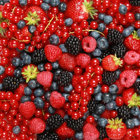 On a table are lying strawberries, bilberries, red currants, raspberries and blackberries