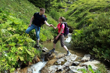 A young male hiker is helping a female hiker to cross a mountain-brook in the German Alps near Oberstdorf.