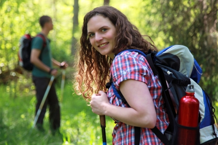 A young woman makes a short break during a Nordic Walking tour