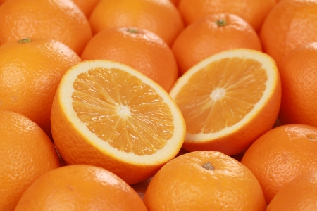 Closeup of sliced fresh oranges, decorated with more oranges