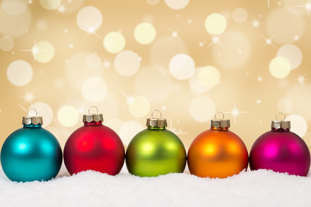 Colorful Christmas balls in a row golden background decoration with snow and copyspace