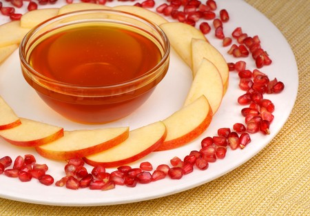 A bowl of honey, apple slices and pomegranate  seeds on a plate with a golden fabric underneath