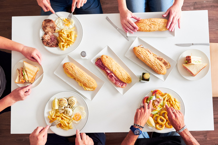 Foto de Overhead view of friends having dinner at a restaurant table. Grilled steaks, French fries, salad, sandwiches and fried squid on white table. - Imagen libre de derechos
