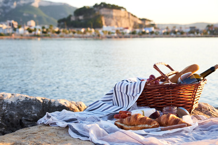 Foto de Romatic picnic on the beach in Denia, Spain. Picnic basket with red wine, bread, jam, cheese and jamon on a sunny day with sea and castle on background. - Imagen libre de derechos