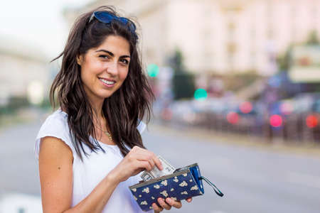 portrait of a beautiful smiling woman holding wallet with money on the street