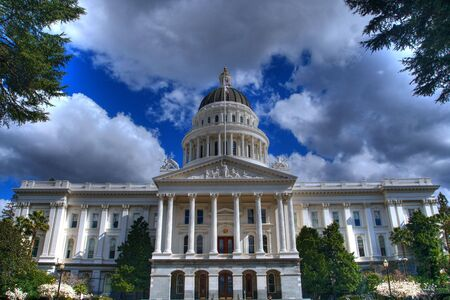 an HDR image of the California State Capital Building from a distance bordered by trees and a blue sky with grey and white clouds
