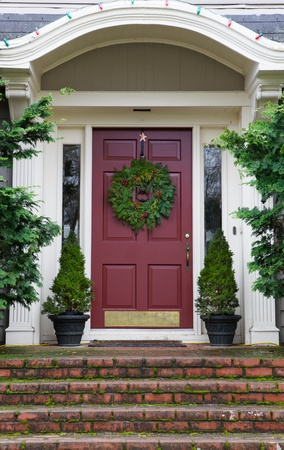 Magenta Door with Wreath on gray home with mossy red brick steps
