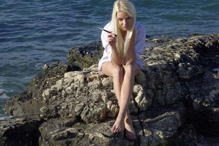 blonde in white with a cigarette near blue sea