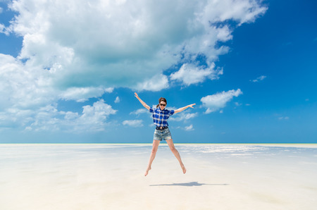 Photo pour Beautiful excited cheerful young woman with arms out in blue cotton checked shirt and sunglasses jumping on the background of desert sea lagoon at white sandy beach in the Caribbean sea, Holbox, Mexico - image libre de droit