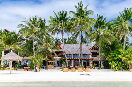 Luxury tropical villa near the sea with beautiful colourful decor surrounding palm trees and lounges in front of it at famous exotic white sandy beach on Boracay island station 1 Philippines