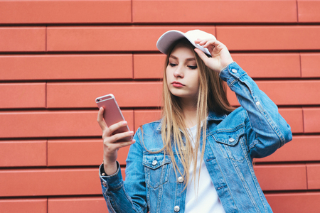 Stylish young blonde in a cap and denim jacket talking on the phone pink color on a red background. Young beautiful woman hipster use a mobile phone