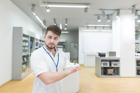 Handsome man consultant in a white T-shirt invites you to the electronics store. Portrait of a concert in a modern technology store. Work of the consultant in the electronics store