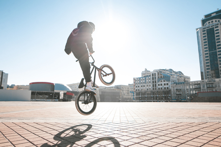 Bmx rider makes a trick on the street on a sunny day. Street bmx freestyle.