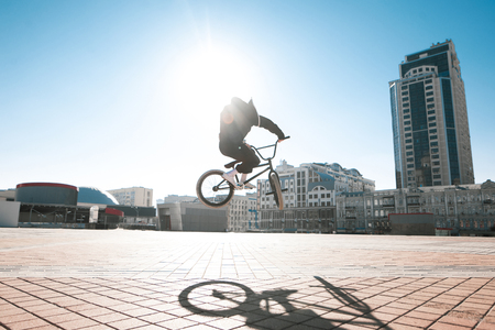Street portrait of a bmx rider in a jump on the street in the background of the city landscape and the sun. Bmx concept. Street freestyle on bmx