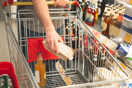 Foto für Man's hand puts the products in an empty cart. Buyer makes purchases in a supermarket. Shopping in a supermarket concept. Buys drinks. Hands and cart close-up. Man buys alcohol - Lizenzfreies Bild