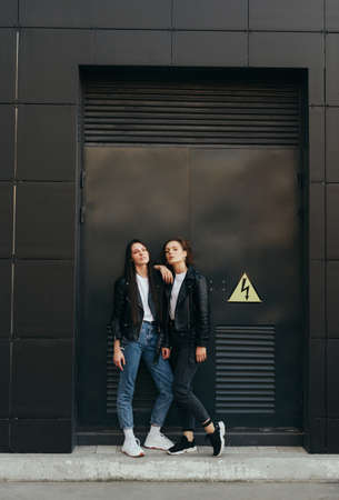 Photo for Vertical photo of 2 stylish young girls in leather jackets standing on black background and posing at camera. Street photo of two girlfriends on dark wall background. Copy space - Royalty Free Image