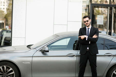 Photo pour elegant businessman standing outside with folded arms, private driver waiting for his boss pointing limousine - image libre de droit