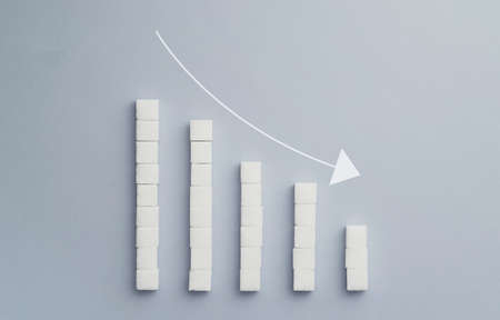 Concept: Negative graph chart made of sugar cubes with an decrease arrow