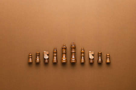 Photo pour Wooden chess figurines organized in a row over brown background - image libre de droit