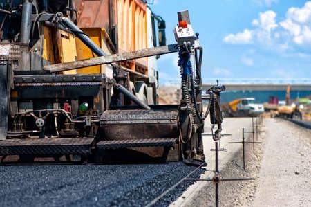 Foto de pavement machine laying fresh asphalt or bitumen on top of the gravel base during highway construction - Imagen libre de derechos