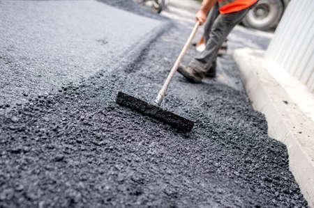 Foto de Worker levelling fresh asphalt on a road construction site, industrial buildings and teamwork - Imagen libre de derechos