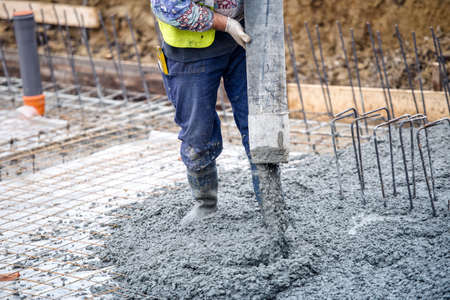 Photo pour building construction worker pouring cement or concrete with pump tube - image libre de droit